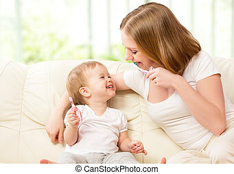 mother and daughter baby girl brushing their teeth together