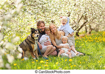 Happy Family and Pet Dog Relaxing in Flower Orchard