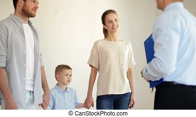 mortgage, housing and real estate concept - happy family and realtor giving house or apartment key and shaking hands with new house owner