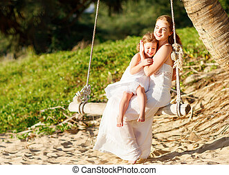 happy family at beach. mother shook child on swing in summer and laughs