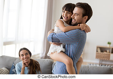 Happy family at home father hold on hands daughter