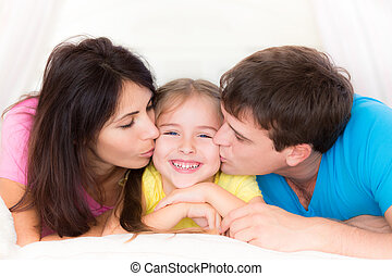Happy family at home - Father and mother kissing your child....