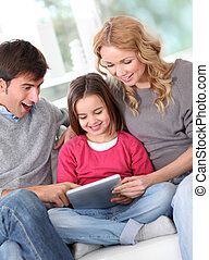 Happy family at home using electronic tablet