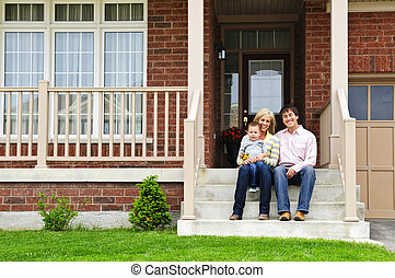 Happy family at home - Young family sitting on front steps ...