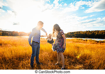 happy family at sunset, having fun with a child in nature