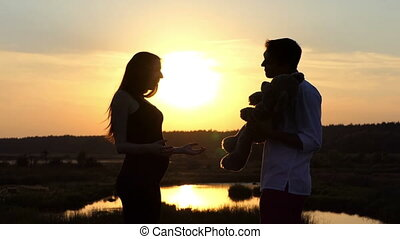Happy family at sunset in slow motion - man give big bear toy to her woman.