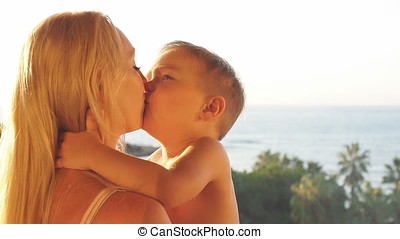 Happy family at sunset. Laughing mother and son in sunset. Slow Motion