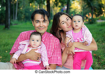 Happy family at the park with father, mother and twins baby - sisters