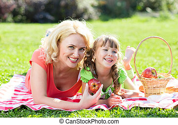 Happy family at vacation concept. Mother and daughter little girl having picnic playing in park outdoors.