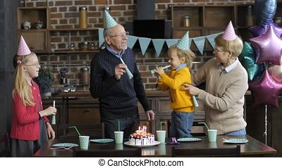 Happy family blowing horns at boy's birthday party