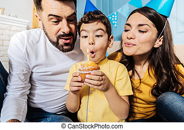 Happy family blowing out candle on birthday muffin together...