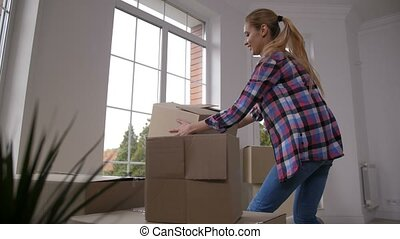 Happy family carrying cardboard boxes in new house -...