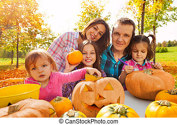 Happy family carving pumpkins prepare to Halloween