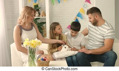 Happy family celebrating Easter and stroking a rabbit