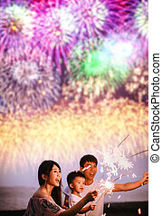 happy family celebrating new year with sparklers on the beach