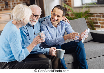 Happy family chatting on the couch while drinking coffee