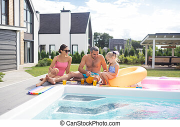 Happy family chilling near the pool on hot summer day