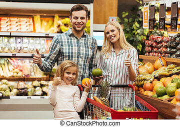 Happy family choosing groceries and showing thumbs up ...
