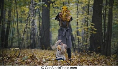 Happy family concept - little daughter with her mother plays with yellow leaves in autumn park, slow-motion