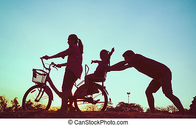 Happy family concpet, Mother and daughter riding with father push a bicycle at sunset