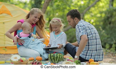 Happy family consisting of four sitting on a picnic, showing little girl how to deal with the tablet