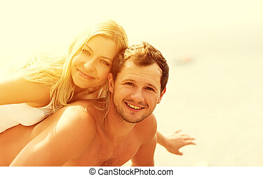 happy family couple in love hugging and laughing on the beach