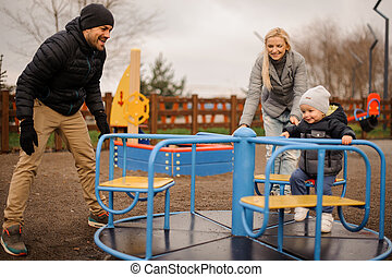 Happy family couple with little son riding on the carousel