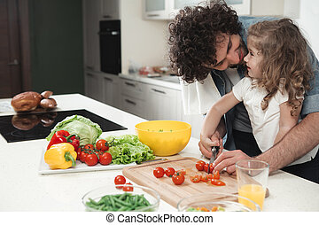 Happy family cutting vegetables for lunch