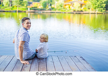 Happy family - Dad and son fishing on the pier