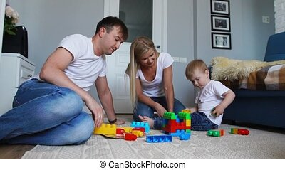 Happy family dad mom and baby 2 years playing lego in their...