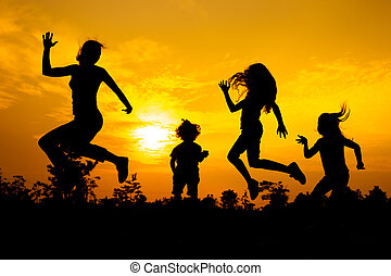 Happy  family dancing on the  road in the  sunset time.