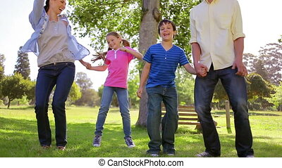 Happy family dancing together on the grass