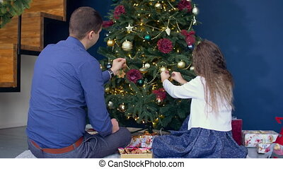Happy family decorating Christmas tree at home - Positive...