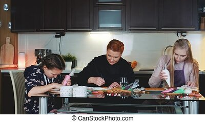 Happy family decorating gingerbread cookies with sugar glaze. Spending evening time together in kitchen at home.