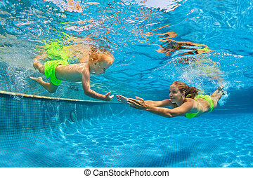 Happy family diving underwater with fun in swimming pool