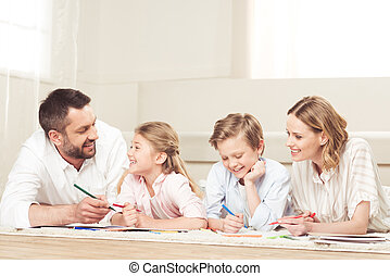 happy family drawing pictures while lying on the floor at home
