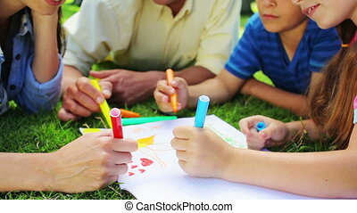 Happy family drawing together while lying on the grass