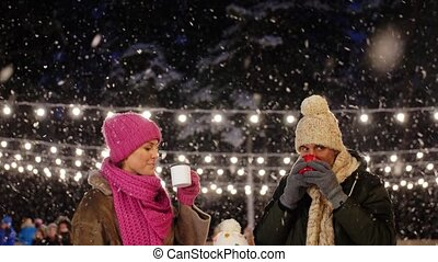 happy family drinking hot tea on skating rink - christmas, ...