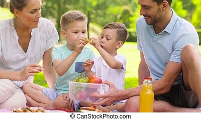 happy family eating fruits on picnic at park - family,...