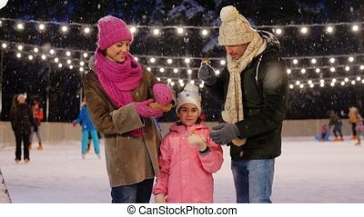 happy family eating pancakes on skating rink - christmas, ...