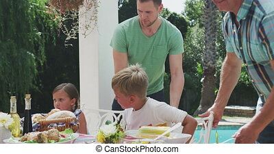 Happy family eating together at table - Front view of a ...