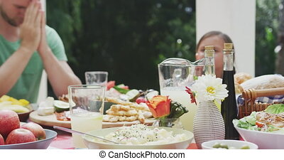Happy family eating together at table - Side view of a multi...