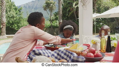 Happy family eating together at table - Side view of an ...