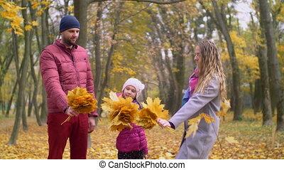 Happy family enjoying beautiful fall season in park - Happy...
