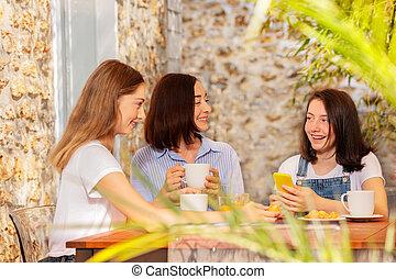 Happy family enjoying breakfast at street cafe