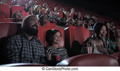 Happy family enjoying comedy in movie theater