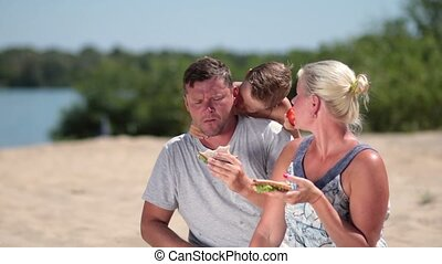 Happy family enjoying lunch on the beach