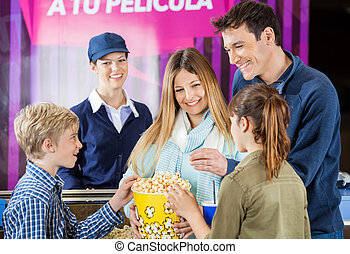 Happy Family Enjoying Popcorn At Cinema Concession Counter