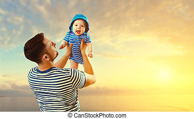 happy family father and baby son on beach by sea at sunset