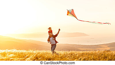 happy family father and child daughter run with kite on meadow
